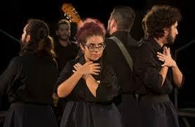 Fotografia colorida, em plano médio, de cinco atores, quatro rapazes e uma moça, em círculo, virados para fora. Eles usam roupas pretas e estão com as mãos cruzadas sobre o peito. Um dos rapazes, no centro, segura um violão.