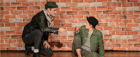 Fotografia colorida dos personagens Matreiro e Oliver, um agachado, o outro sentado no chão. Matreiro, um jovem de pele clara e cabelos curtos, usando um pequeno chapéu esverdeado com abas curtas, lenço bege no pescoço, casaco de couro, calça justa e sapatos pretos, está à esquerda, com a mão direita estendida em direção a Oliver. Oliver, um menino magro de pele clara, usando um quepe preto com a aba levantada, jaqueta verde sobre camiseta branca e preta, calça cinza amarrotada com a barra dobrada, está sentado no chão segurando uma maçã, olhando para Malheiro. Ao fundo uma cortina simula um muro de tijolos avermelhados.