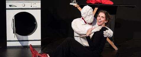 Fotografia colorida sobre fundo preto da personagem Nana, interpretada por Andi Rubinstein abraçada com um grande boneco branco, sentada no chão. Andi é uma mulher de pele clara, cabelos louros ondulados presos em  uma trança e olhos verdes. Veste blusa de mangas longas e calça pretas e botas vermelhas. Ao fundo, à esquerda, uma máquina de lavar roupas com a porta aberta e uma tábua de passar roupas com um pano vermelho em cima.